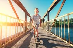 Boy skates on skate board on the bridge over tthe river royalty free stock photo