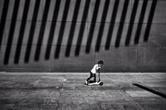 A boy skating besides a wall with many shadow lines Royalty Free Stock Image