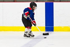 Boy skating with the puck at ice hockey practice Stock Images