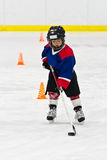Boy skating with the puck at ice hockey practice Royalty Free Stock Image