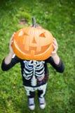 Boy in skeleton costume holding pupmkin. At halloween royalty free stock image