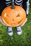 Boy in skeleton costume holding pupmkin. At halloween stock image