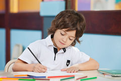 Boy With Sketch Pen Drawing In Kindergarten Stock Photos