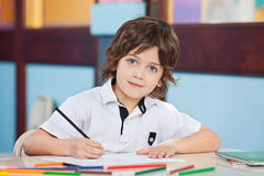 Boy With Sketch Pen And Paper At Desk Royalty Free Stock Images