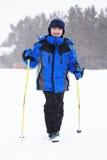 Boy with ski sticks and snowfall Stock Photo