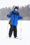 Boy with ski sticks and snowfall Stock Photos