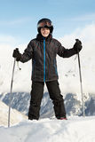 Boy in ski suit stands leaning on ski poles Royalty Free Stock Images