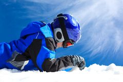 Boy in ski wear. Lying in the snow against a bright blue sky Stock Photography