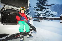 Boy skier sitting in the car trunk during snowfall Stock Photos