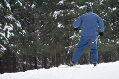Boy skier in a ski suit and hat standing on snowy slope . royalty free stock photography