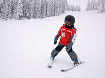 Boy skiing. Doing snowplow down the ski hill, wearing helmet Royalty Free Stock Images