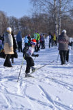 Boy skiing and a group of people in a winter park. Royalty Free Stock Photos