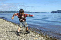 Boy skips a rock in the water. Stock Images