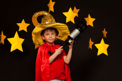Boy in sky watcher costume with telescope Stock Images