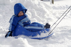 Boy on a sled. A toddler boy getting pulled on his sled on freshly fallen snow Stock Photos