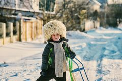 A boy with a sled on a cold day. Boy on a cold day in a big fur hat Royalty Free Stock Images
