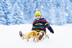 Boy on sled ride. Child sledding. Kid on sledge. Little boy enjoying a sleigh ride. Child sledding. Toddler kid riding a sledge. Children play outdoors in snow royalty free stock image