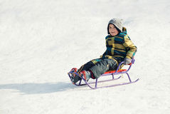 Boy On A Sled In The Snow Stock Photo