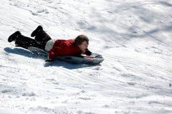 Boy sledding. A boy sledding down a snow covered hill Stock Photos