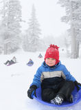 Boy sledding. Four year old boy sledding in snowy landscape Royalty Free Stock Photography