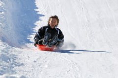Boy Sledding Down the Hill. Boy sledding fast down the hill with snow background Stock Photo