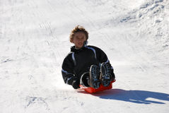 Boy Sledding Down the Hill. Boy sledding fast down the hilll with snow background Royalty Free Stock Photos