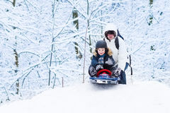 Boy sledding down hill with his father helping him. Little boy sledding down a hill with his father helping him in a snowy winter park royalty free stock photos