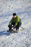 Boy Sledding Down Hill In Winter Stock Images