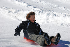 Boy Sledding Fast Down the Hill on a Red Sled stock photography