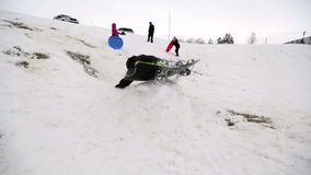 Boy sledding off jump stock video footage