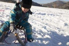 Boy sledding on snow Royalty Free Stock Images