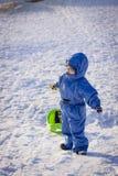 Boy with sledge on snow Stock Photos