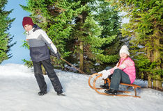 Boy sledging girl to a hill in the winter forest Royalty Free Stock Image