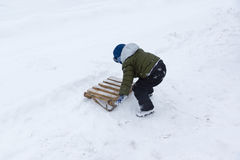 Boy with sleds are made of planks Royalty Free Stock Image