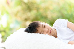 Boy sleep on bed. Selective focus at young Thai boy sleep on the white bed with out focus background of green plant Stock Photos
