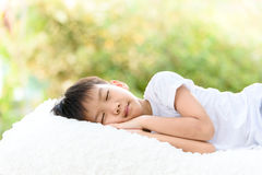 Boy sleep on bed. Selective focus at young Thai boy sleep on the white bed with out focus background of green plant Stock Image
