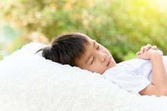 Boy sleep on bed. Selective focus at young Thai boy sleep on the white bed with out focus background of green plant Stock Images
