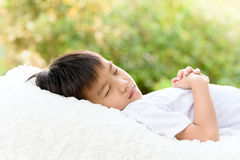 Boy sleep on bed. Selective focus at young Thai boy sleep on the white bed with out focus background of green plant Royalty Free Stock Image