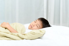 Boy sleep on bed. Young Thai boy sleep on the white bed in the bedroom Stock Photo