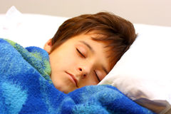 A boy sleeping. With blue blanket on a white pillow Stock Photos