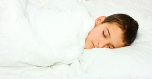 A boy sleeping. With white blanket on a white pillow Royalty Free Stock Images