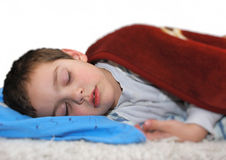 Boy sleeping. A boy is sleeping on a bed covered with a blanket Stock Photos