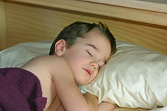 Boy Sleeping in Bed Stock Image