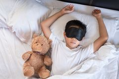 Boy sleeping on bed with teddy bear white pillow and sheets wearing sleep mask Royalty Free Stock Photos