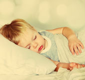 Boy Sleeping on a Bed. Toned. Little Boy with Fair Hair Sleeping on a Bed. Effect bokeh and toned Stock Photos