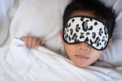 Boy sleeping on bed white pillow and sheets with sleep mask. Boy sleeping peacefully.sleep concept Stock Images