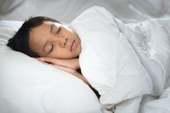 Boy sleeping on bed with white sheet and pillow. Asian kid fall asleep daydreaming.sleep concept Stock Photo