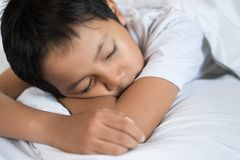 Boy sleeping on bed with white sheet and pillow. Asian kid fall asleep daydreaming. Sleep concept Royalty Free Stock Photography