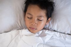 Boy sleeping on bed with white sheet and pillow. Asian kid fall asleep daydreaming. Sleep concept Stock Photo