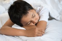 Boy sleeping on bed with white sheet and pillow. Asian kid fall asleep daydreaming.sleep concept Royalty Free Stock Image